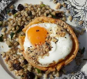 Pumpkin Haloumi tart with grains and a fried egg.